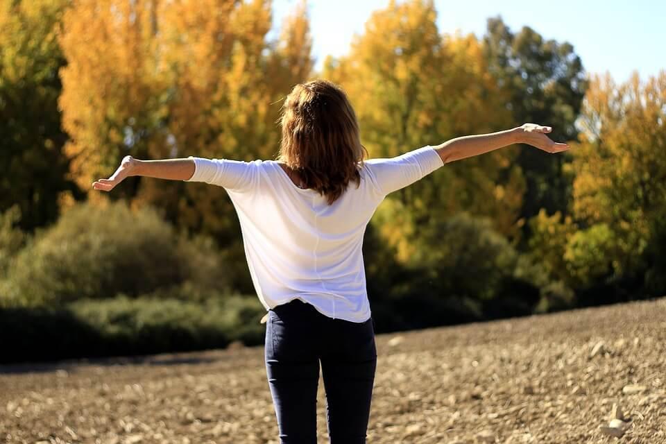 На фото изображена девушка со спины с распростертыми руками на фоне деревьев.