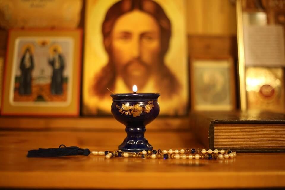 На фото изображены иконы и зажженная лампадка на столе.