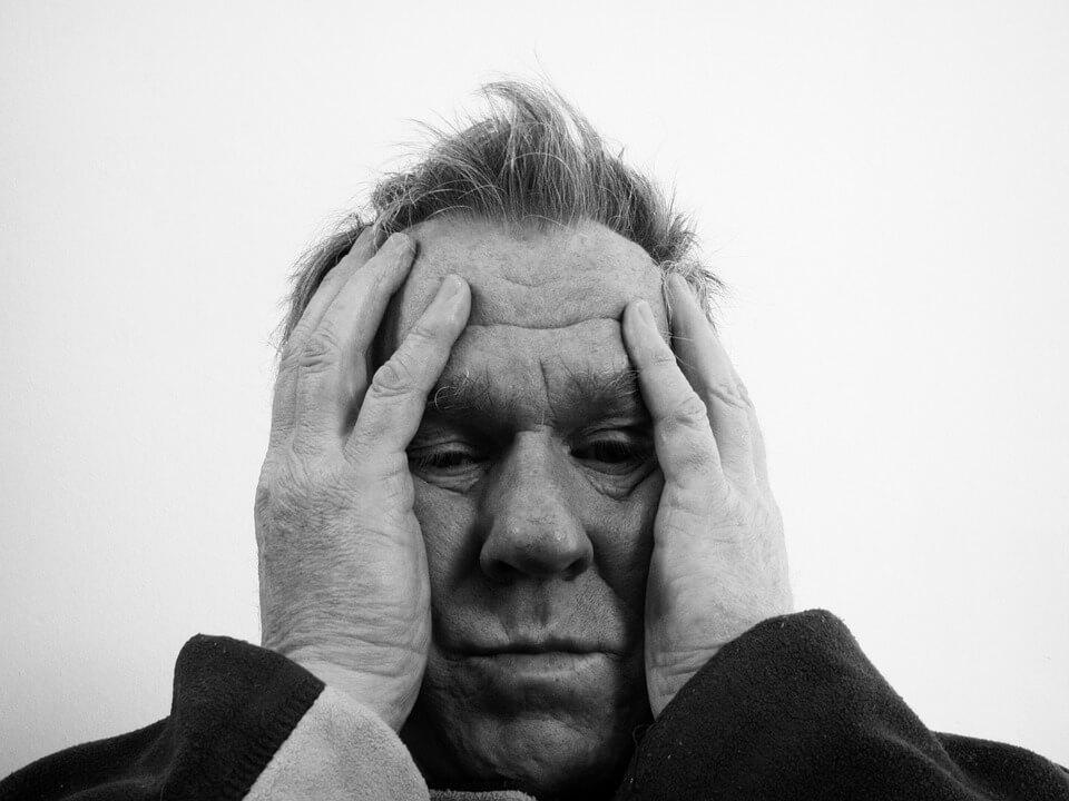 На фото изображен мужчина, обхвативший голову руками.