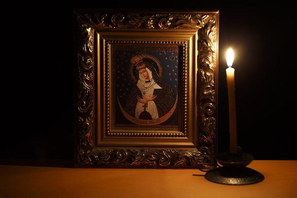 """На фото изображена икона """"Остробрамская"""" и горящая свеча, которые стоят на столе."""