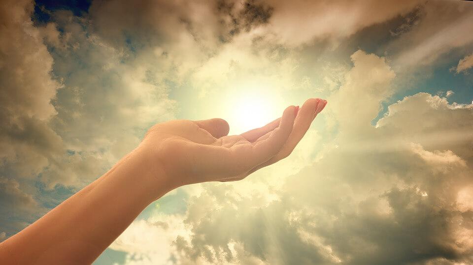 На фото изображен свет в небе и рука, которая к нему тянется.