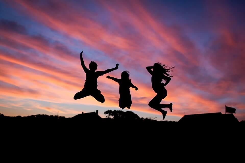 На фото изображены силуэты трех человек в прыжке на фоне неба.