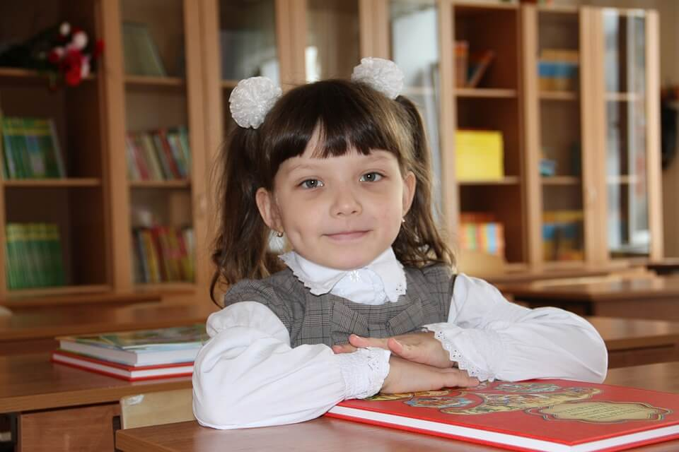 На фото изображена ученица за партой в школе.