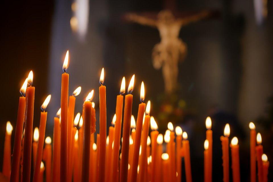 На фото изображены горящие свечи в церкви.