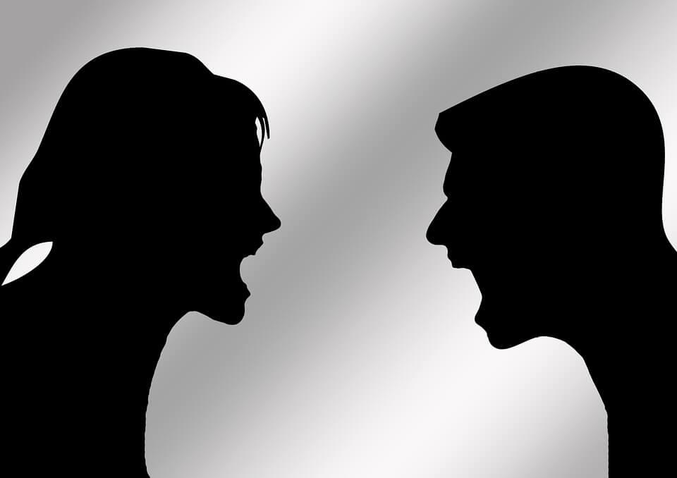На фото изображены силуэты мужчины и женщины, которые спорят.