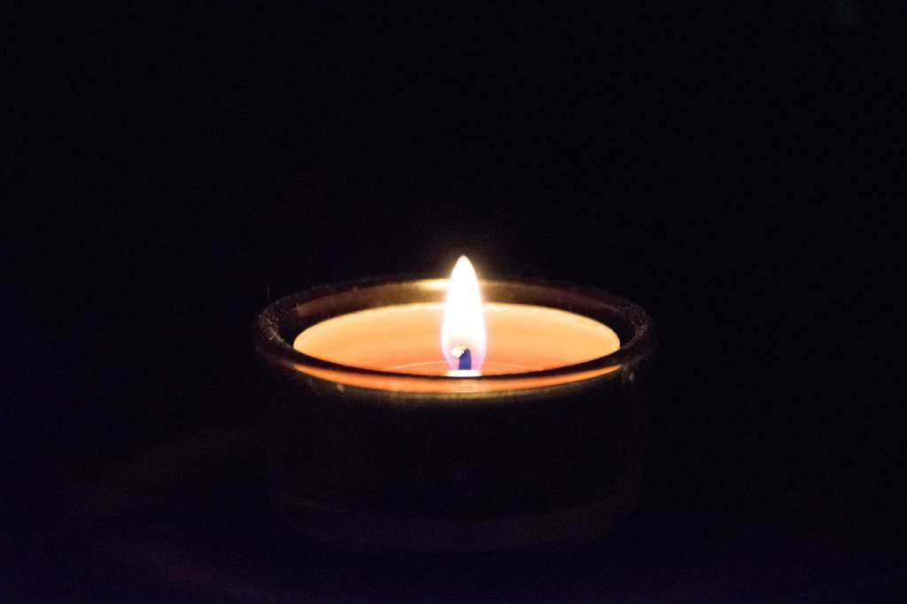 На фото изображена свеча в ночное время.