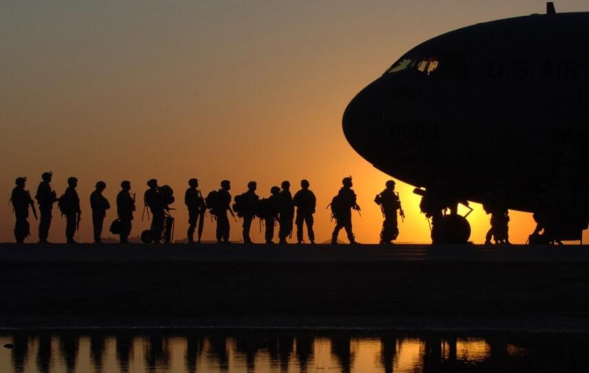 Военные и самолет на фоне заката.