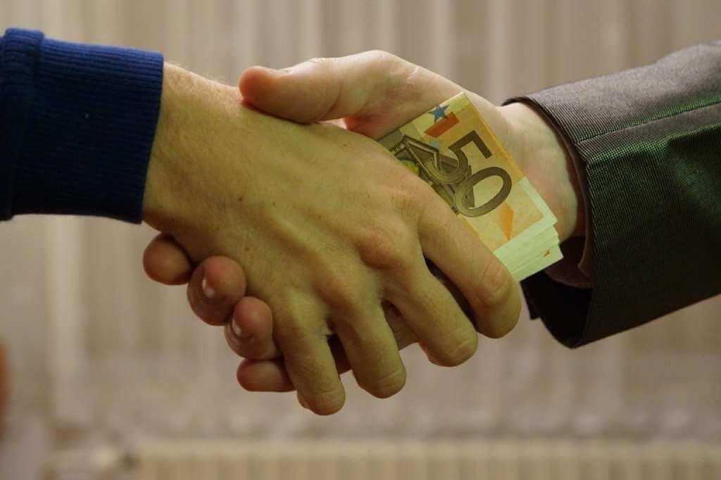 На фото один человек передает деньги другому.