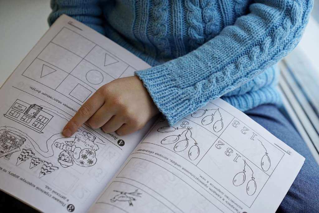 На фото мальчик изучает книгу.