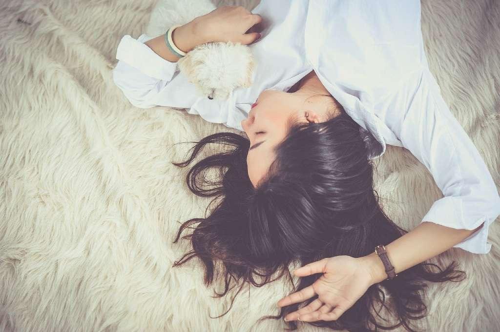 На фото девушка спит с собачкой.