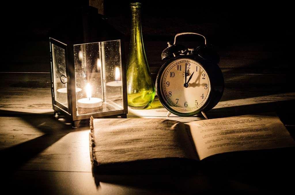 На фото изображена книга, будильник и лампа на столе.